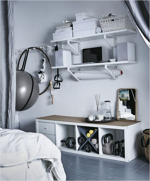 Workout equipment is stored on the wall of a bedroom on hooks and shelves.