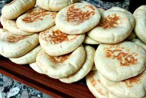 Moroccan pita bread stacked on rack - Christine Benlafquih