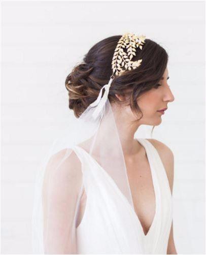 Acconciatura per capelli raccolti da sposa con diadema e velo