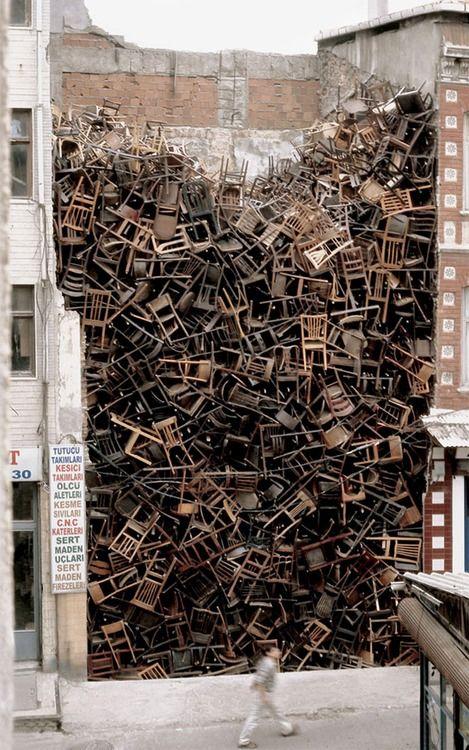 1555 stacked chairs between buildings by Doris Salcedo