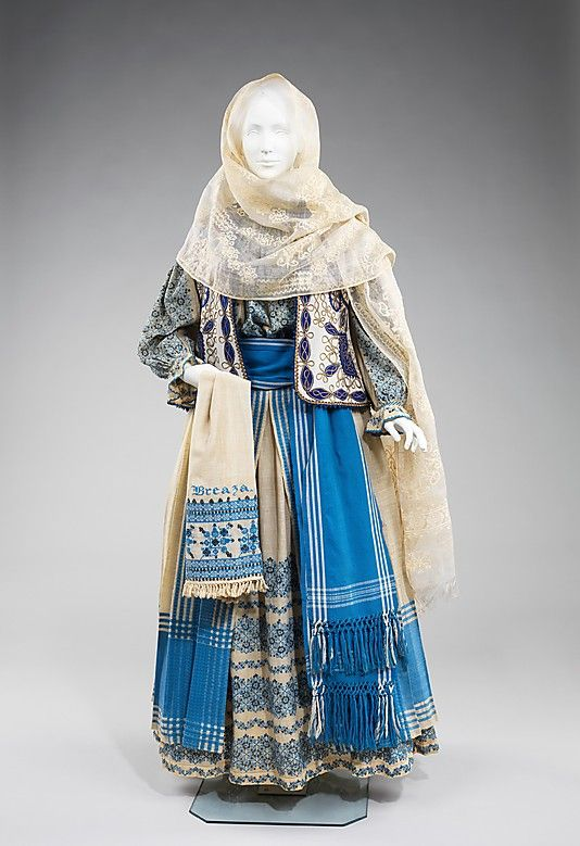 "Romanian folk costume has remained relatively unchanged and continues to be worn for festival occasions. The basic model for women consists of an embroidered blouse and skirt, belt, head scarf, and often a vest or jacket. As in many cultures, embroidery is placed at ""vulnerable"" areas of the body: the neck, cuffs, and hem, but also at the shoulders and sleeves as a symbol of strength. This example of a full festival costume is striking in the variation of blue tones and abundant embroidery."
