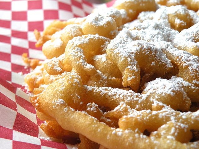 Funnel Cake  1 large egg 2 cups milk 1 teaspoon vanilla 2 cups flour 1 1/2 tablespoons sugar 1 teaspoon baking soda 1 teaspoon salt 4 tablespoons melted butter 2 quarts peanut or canola oil powdered sugar
