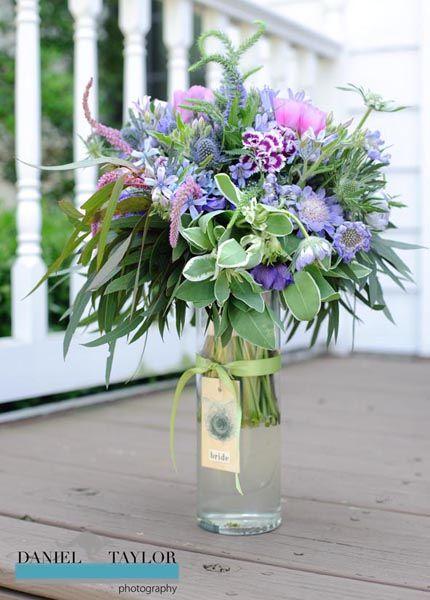 delicioso ramo de flores silvestres en tonos malva y rosa con delphinium y amapolas
