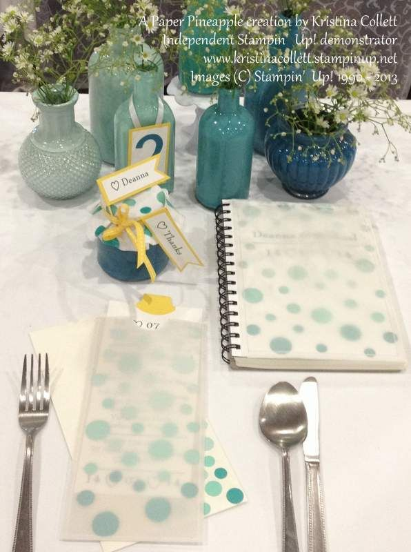 """""""Teal ombre"""" wedding setting with DL sized invitation with vellum pocket and matching envelope, placecard tag, guest book, centrepiece and table number."""