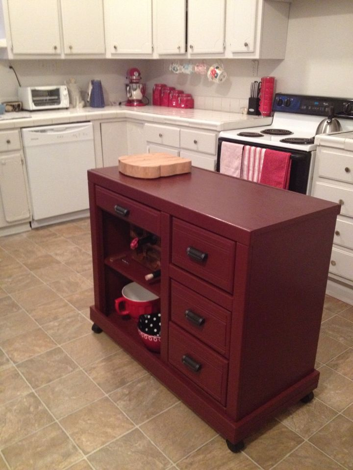 A kitchen island made from a desk--casters on the bottom make it mobile for versatile use. Good for a narrow space and more drawers!