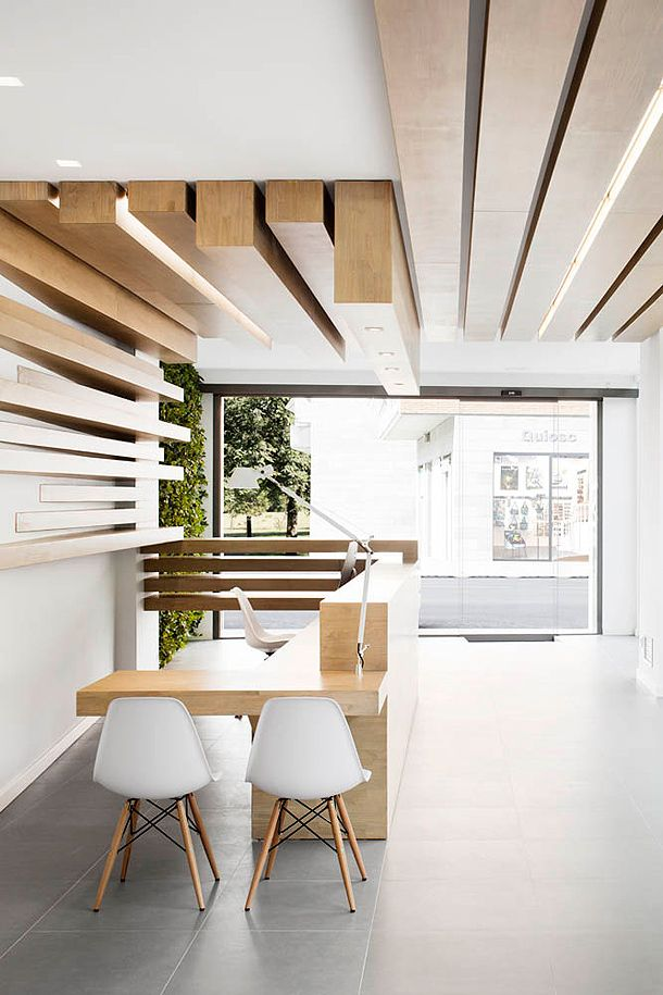 Recepción luminosa y blanca con techo y pared decorativos de madera, y mostrador a medida.