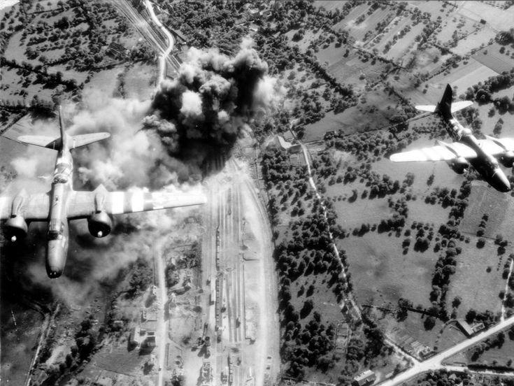 """Deux bombardiers bimoteurs américains bombardent la gare et le réseau ferroviaire de Domfront (Orne). Les voies de chemin de fer ont disparu aujourd'hui. Il s'agit de deux Douglas Havoc A-20G du 416th BG 671st BS 97th Combat Bombardment Wing du IX Bomber Command de la 9th Air Force. Présence des """"bandes d'invasion"""" donc après le 5 juin 1944."""