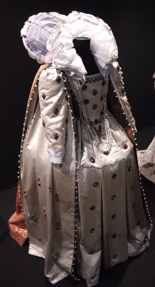 Robe élisabéthaine à tambour en satin de soie crème décoré de perles  et de cabochon sur le devant. Corsage bordé au décolleté d'un galon or incrusté de perles  avec dépassement de lingerie. Pointe du corsage galonné or incrusté de perles, topaze et rubis. Côté  et dos en satin. Chérusque en forme de paillon en crin blanc, brodé dentelle argent.