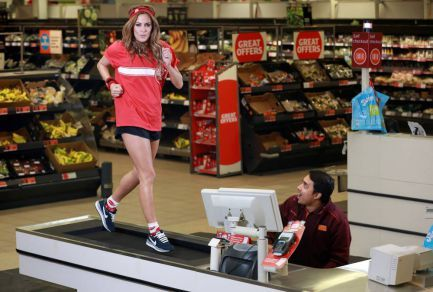 General Merchandiser, Asif Hossain, watches television presenter Caroline Flack show off this yearís Sport Relief merchandise during a last minute training session on a checkout treadmill, at a Sainsbury's store in Whitechapel, east London, ahead of the Sainsbury's Sport Relief Games, which take place on Friday 21st until Sunday 23rd March. The merchandise is available in Sainsburyís stores nationwide. Photo credit should read: Matt Alexander/PA Wire  www.setwo.co.uk