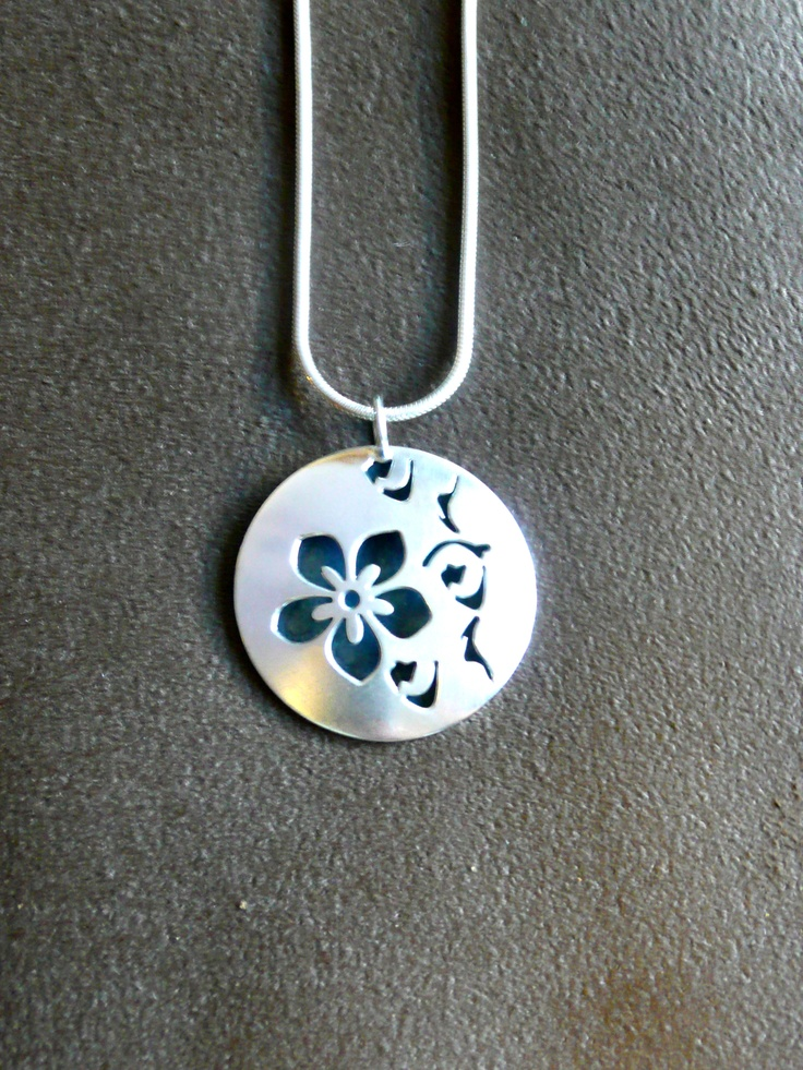 "Hollow Domed Round Cherry Blossom Necklace.  The necklace is made of sterling silver, domed, hollow, round disks which are 1 1/4"" in diameter. They are pierced with a design of cherry blossoms and oxidized inside the hollow form to make the design stand out using contrast. The chain is also made of sterling silver."
