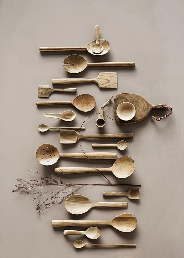 A collection of raw, carved spoons, scoops and wooden boards
