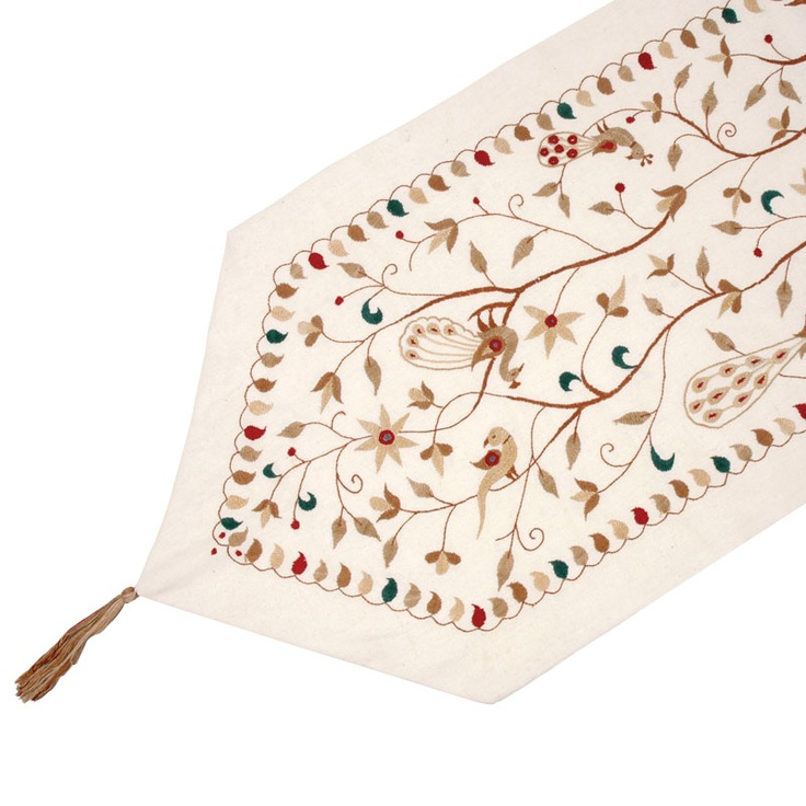 Curious peacocks and pheasants nestled amongst the foliage make this a truly distinct table runner for any occasion. Handmade by gifted artisans in India, this cotton runner features a beautifully embroidered scene in red, green, cream and tan set off by a lovely leafy border. With its pretty details and bright colours, this runner will make any coffee or dinner table a fresh place to serve your guests.