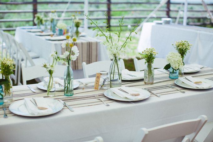 Brides: Rustic White and Burlap Tablecape. Reception tables were draped in white linens and accented with burlap table runners. Mason jars filled with candles and wildflowers—including rosemary, lavender, daisies and Billy balls—dotted the table tops.