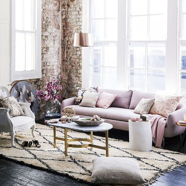 A romantic industrial living room with pink sofa