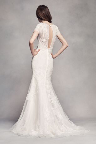 Effortlessly chic and modern. This veiled lace short sleeve sheath wedding dress is thoughtfully detailed with corded lace and delicate…