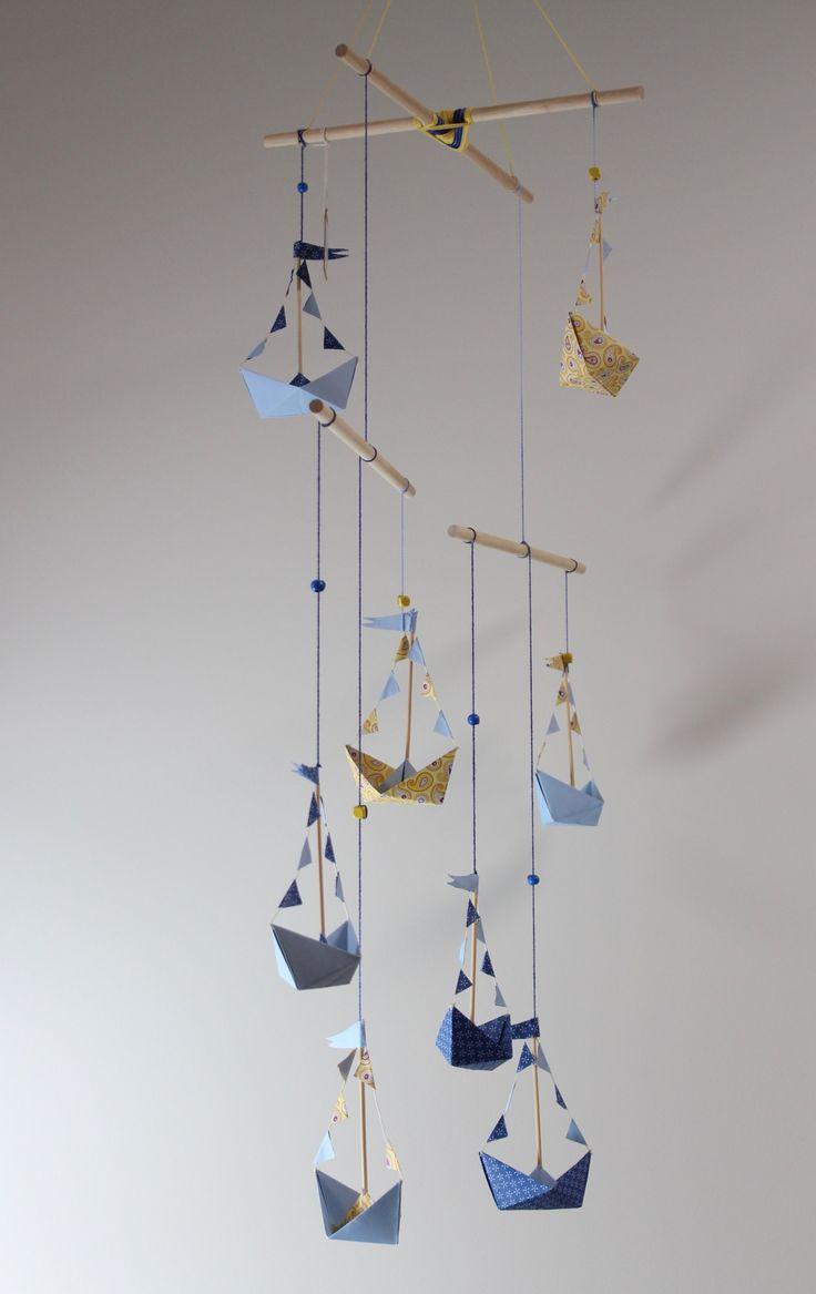 Móvil de Barcos de papel, compuesto por 8 barquitos, con técnica de origami en tonos azules y amarillos, móvil modelo Alexander Calder, la característica de este móvil es el equilibrio. Terminado en la parte superior con un ojo de Dios. Ideal para decorar la habitación de los niños. Dimensiones: 52x75cm.(La dimensión del móvil es desde el bastidor hasta la pieza final)