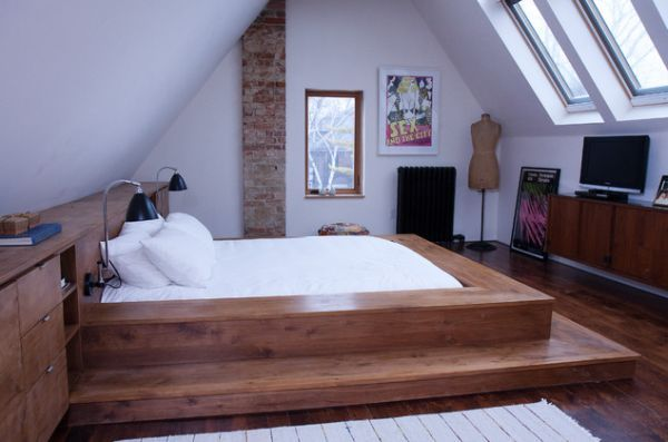 A sunken bed raised on a wooden platform with a very modern and cozy look