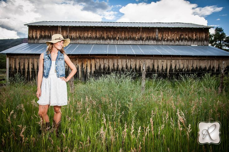 Country senior pictures with old barn in a field