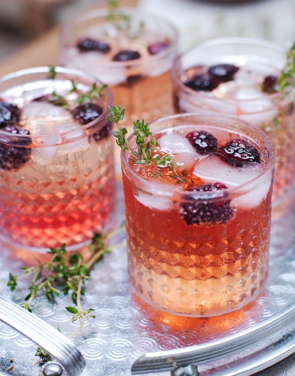 Pynt cocktailglass med friske bær og urter.