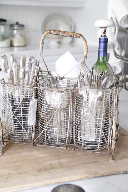 This is a unique french wire bottle carrier holding our everyday staples of hotel flatware, napkins and wine.