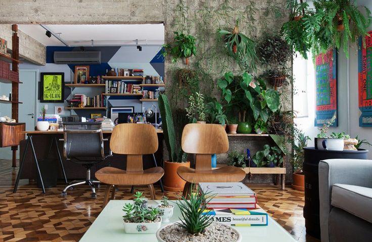 Sala de estar com estrutura de concreto aparente onde foi instalado um pequeno jardim vertical.