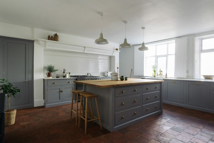 This open plan deVOL Shaker kitchen features grey painted cupboards, simple white walls, aged terracotta tiles and rustic accessories