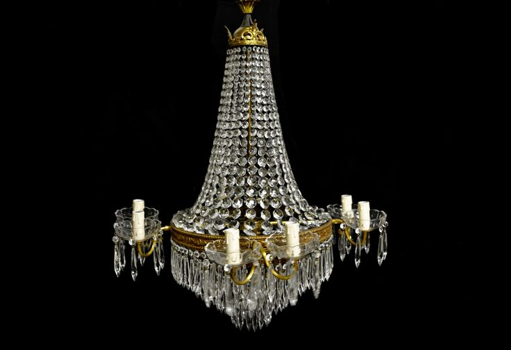 This brass Italian Empire chandelier has 12 lights. Octagonal botton chains hang from the top to the central frame part of the chandelier. A waterfall bottom is covered all around by icicle cut crystal drops. Glass cups holding icicle drops are placed on the arms of the chandelier.