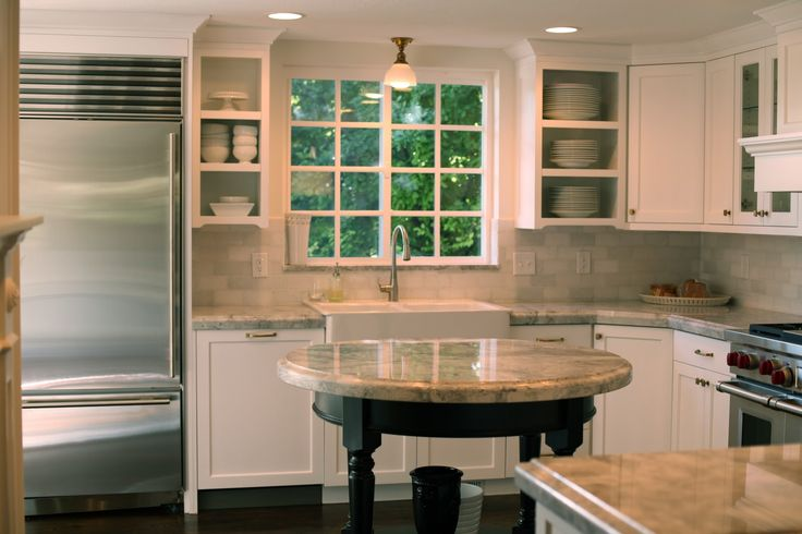 Round kitchen island with shelf, so practical. No bumping corners, extra seating for dinner when overflow, great for traffic patterns in smaller kitchen.