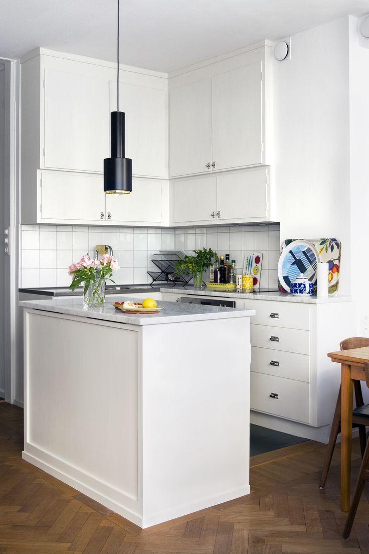 Måttbyggt funkiskök med snedställda underskåp och fristående köksbänk.