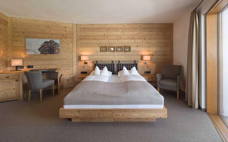 Camera da letto con pareti di legno e letto matrimoniale con cuscini bianchi e coperte grigie