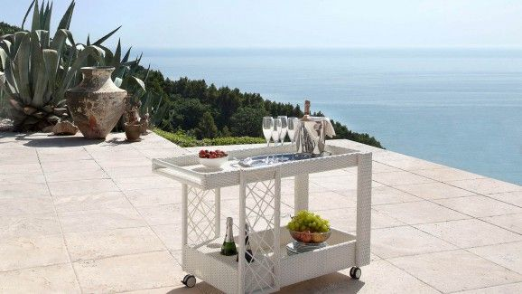 100% Made In Italy. Outdoor serving trolley for outdoor, designed by Roberto Serio. The metal structure covered with wicker fibre (synthetic rattan) is available in white or dark rattan.