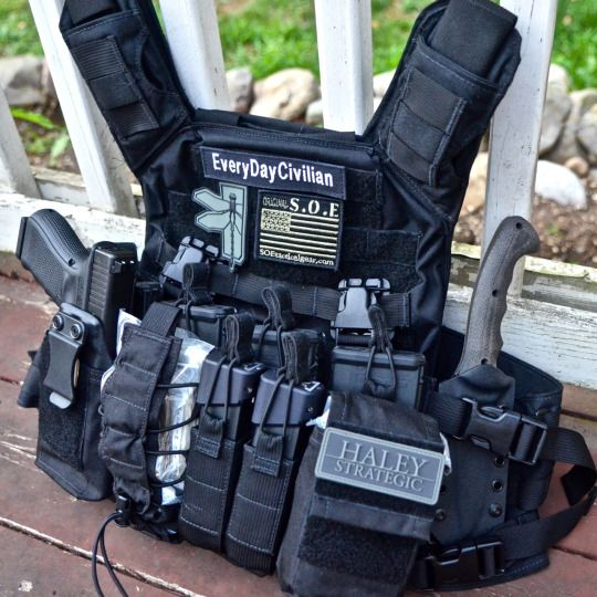 Close-up of Shellback Tactical Banshee Plate Carrier with AR500 Curved Plates with Haley Strategic D3CR. The D3 loadout: Glock 19 Gen 4 with custom holster mounted in GP pouch, Magpul Pmags, Glock 17 Mags with Taran Tactical Innovations +6 base pads, Winkler Knives II Combat Knife, and Tactical Response VOK located in GP; Bungee Pouches