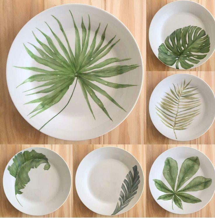 Watercolor like underglaze leaves on white ceramic plates.