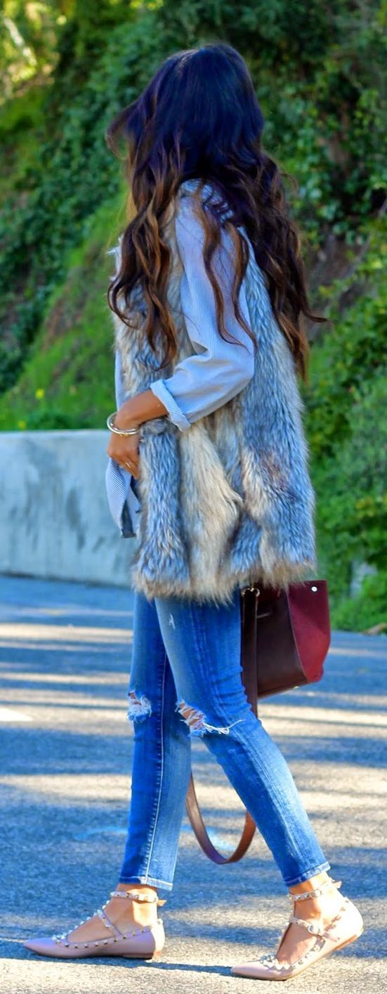 Long fur vest, flowy button up and distressed jeans.