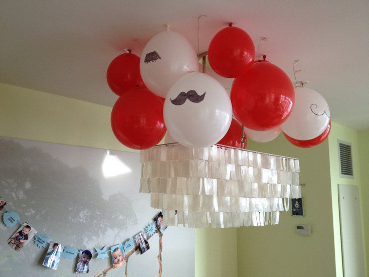 Balloons taped to ceiling with mustaches drawn on them
