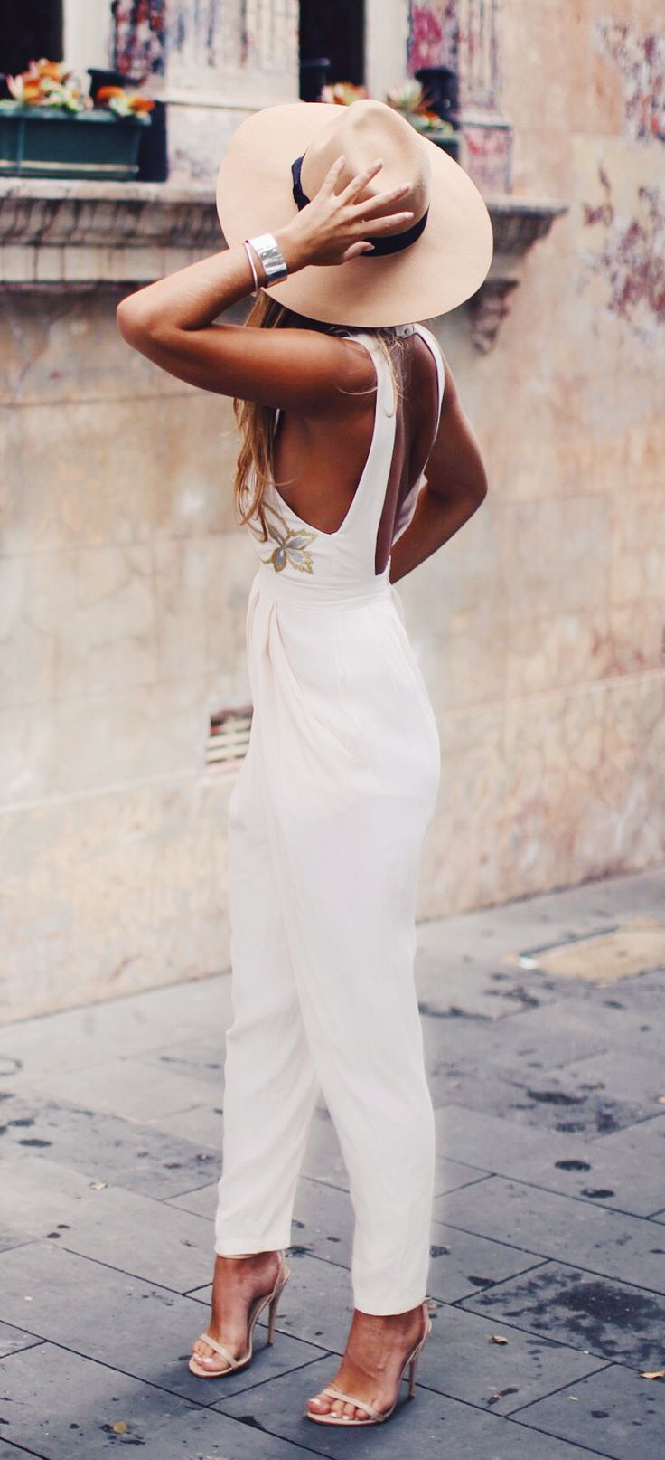 Natasha Oakley is wearing a white jumpsuit from Alice McCALL, shoes from Steve Madden and a hat