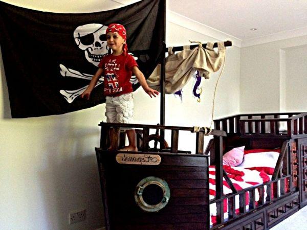 kinderbett-pirat-fahne - klein junge auf dem bett