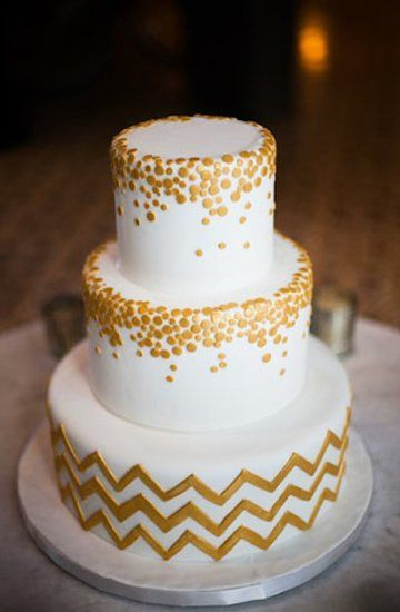 : An all-white cake is given a graphic touch with a chevron base and metallic circles.