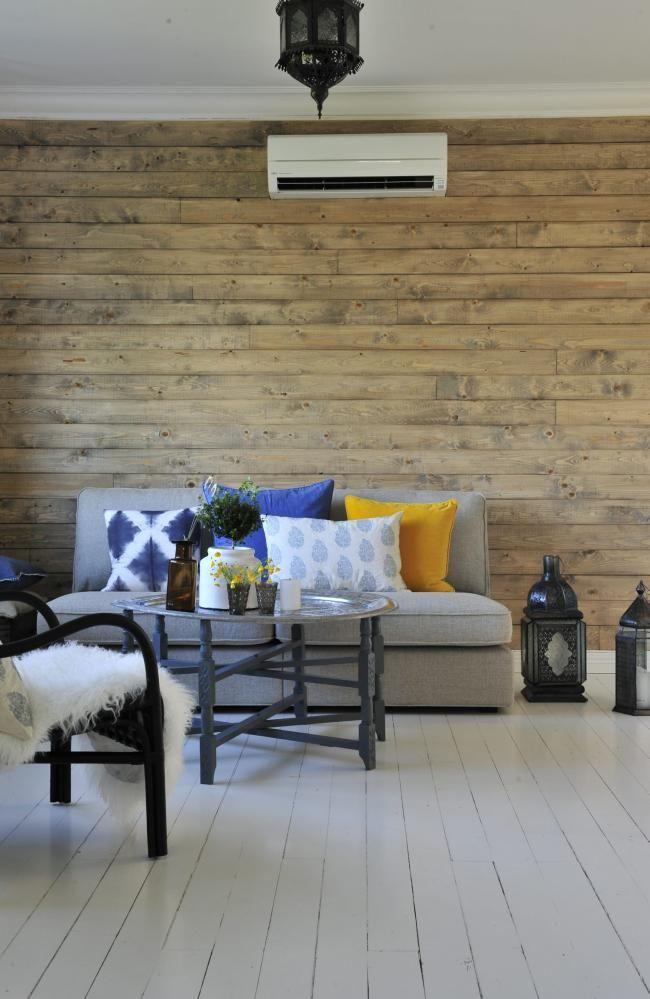 RUSTIKK LOOK: Den fine veggen har eierne stått for selv. De la først panel av samme typen som man bruker under tak, før de beiset det med et strøk Lady drivved fra Jotun. Sofaen er fra Ikea, bordet fra Tine K. Lyktene fra Kremmerhuset.