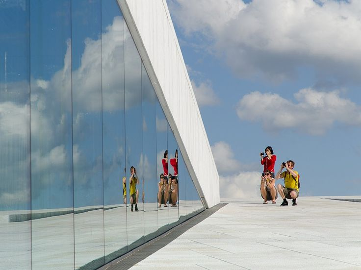 """Getting Their Shot Photograph by Wim Uyttenbroeck, National Geographic Your Shot  """"The Oslo Opera House is a very special place,"""" writes Wim Uyttenbroeck, who captured this picture in the Norwegian capital. """"These three colorful photographers make a nice contrast against the white stone and plate glass of the building. The white clouds in the sky make the picture complete."""