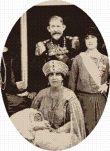King Ferdinand and Queen Marie of Romania at the christening of their grandson Prince Peter (later king) of Yugoslavia, 1923.  The lady at the right is the young Duchess of York, later Queen Consort of Great Britain.