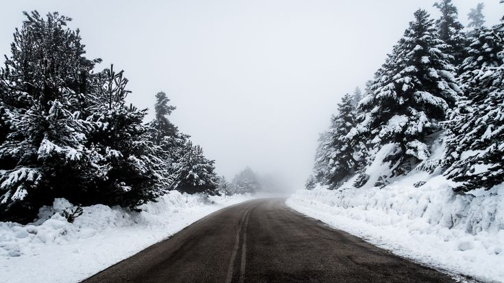 Looking down a clean road in Ziria, Greece with snow covered banks and trees on the sides