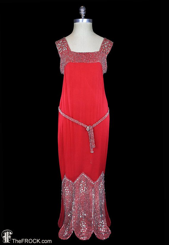 1920s crinkled silk chiffon gown decorated at top, middle, and bottom with tiny silver sequins and glass beads. The skirt is beaded from chevron to scallop at front and back, the sides are both open with walking slits the length of the beadwork. Crepe de chine interior.