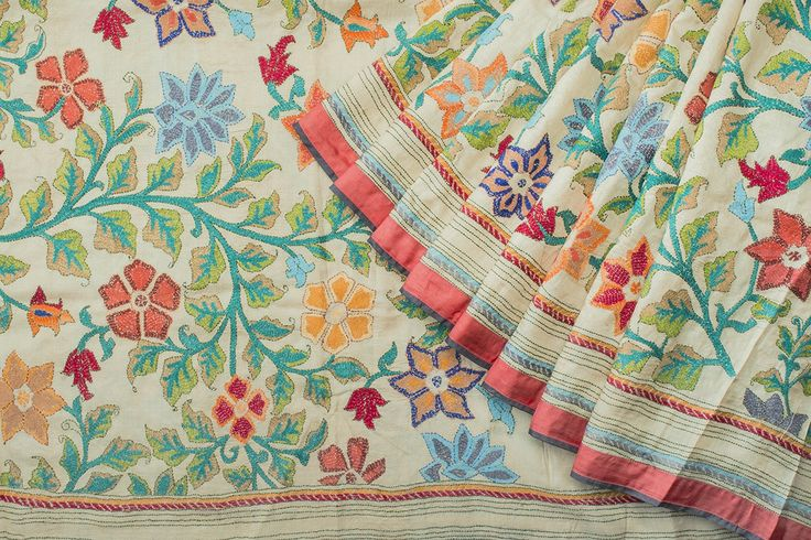 Cream colored Tussar sari with hand embroidered Kantha work in multi colored floral pattern all over the body.