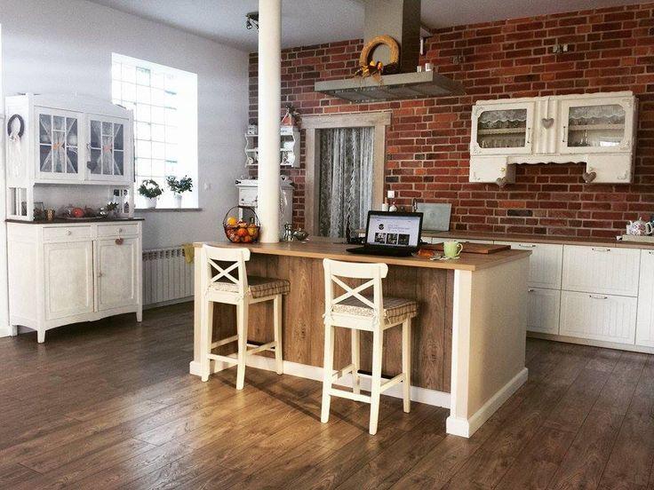 Aranżacja przestronnej kuchni z wygodną wyspą i charakterystycznymi cegłami na ścianie. Drewniana podłoga i drewniane...