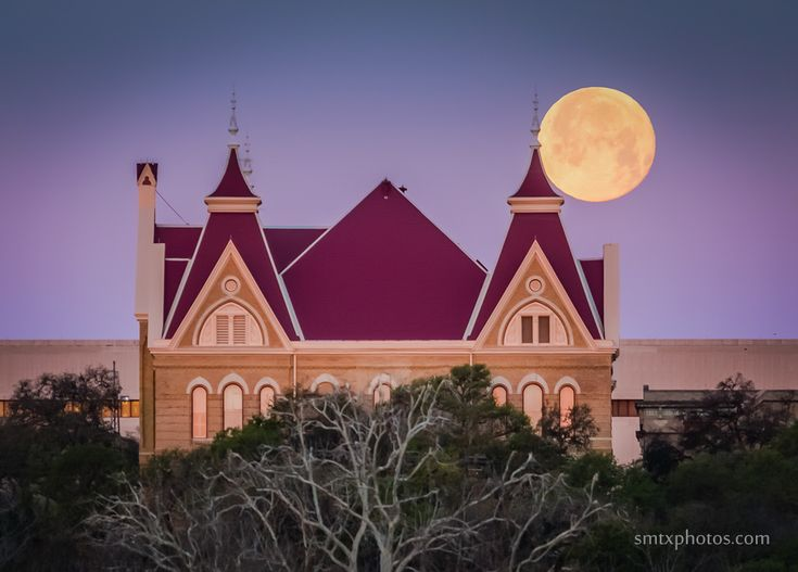 The full moon sets behind Old Main on the Texas State University Campus in San Marcos, TX.