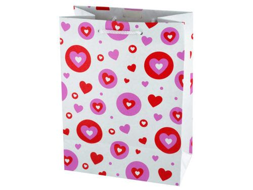 """Perfect for Valentine's Day and other occasions, this Medium Craft Hearts Gift Bag features a matte white paper bag with a fun pink and red hearts and dots print and white nylon handles. Measures approximately 7"""" x 4"""" x 9.375"""". Comes loose."""