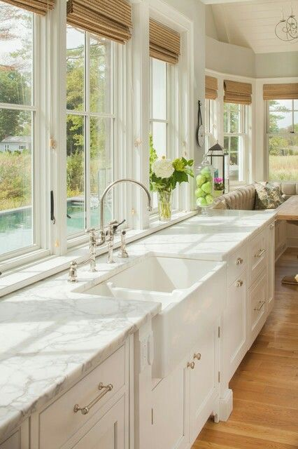 Love the long windows with the counter and bright white cabinets