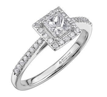 Perfectly matched with a PureWhite Gold setting, an 18ct Canadian gold and palladium alloy which allows your ring to have a bright white colour, this stunning engagement ring features a gorgeous cushion cut diamond surrounded by a square shaped halo of smaller brilliant cut stones, which is further enhanced by glittering diamonds set on the shoulders.