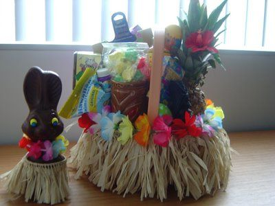 Tiki themed Easter basket. Inside the basket is a mug, lucky tiki idol, little tropical toys, Hawaiian snacks, a pineapple, and traditional Easter candy. I added the grass skirt and flowers to a plain Easter basket.The Easter bunny was a regular Parsnip Pete hollow chocolate bunny, and I gave him a lei and grass skirt